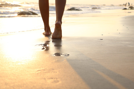 Girl walking on wet sandy beach leaving footprints in the sand at sunset time