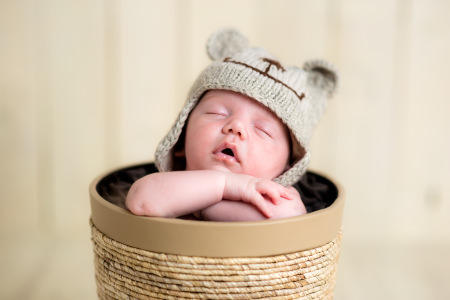 Front view of a cute white Caucasian newborn baby boy sleeping in a decorative basket, crossed hands under the chin holding his head, wearing a hand knitted bear like wool hat. Shot on Canon EOS into a studio, selective focus with sharp peak on baby's face. Warm toned edit to emphasize overall softness feel.